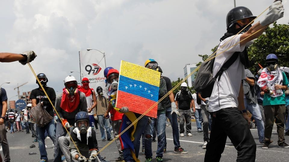 Opposition supporters uses a giant sling shot to throw a