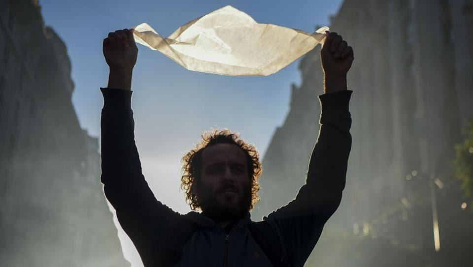 A demonstrator carrying a white headscarf  as he  represents the Madres de Plaza de Mayo human rights group march to the Plaza de Mayo square in downtown Buenos Aires.Thousands of Argentines of all ages and opposing political parties joined to protest a Supreme Court ruling that many feared would lead to the release of convicted human rights criminals. (Eitan Abramovich/AFP)