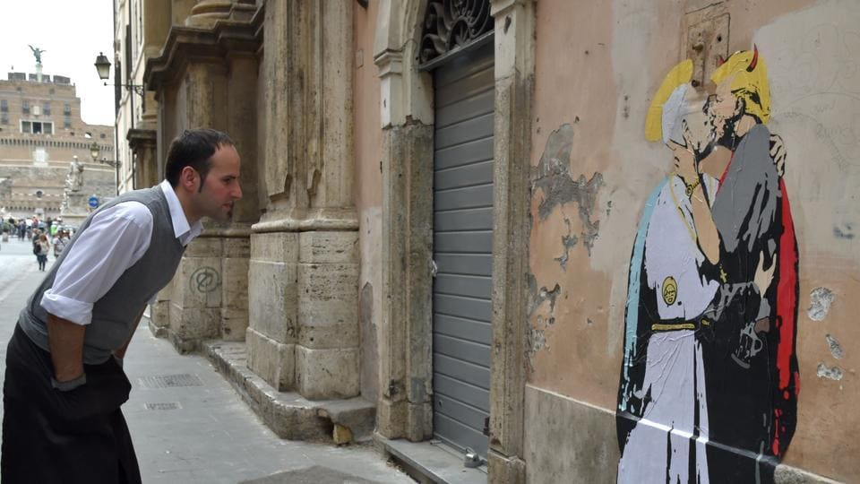 A waiter looks at a collage showing Pope Francis kissing US President Donald Trump near Castel Sant'Angelo in central Rome.
