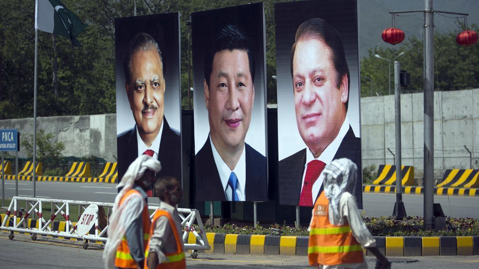 In this April 20, 2015 file photo, municipality workers walk past a billboard showing pictures of Chinese President Xi Jinping, center, with Pakistan's President Mamnoon Hussain, left, and Prime Minister Nawaz Sharif on display during a two-day visit by the Chinese president to launch an ambitious $45 billion economic corridor linking Pakistan's port city of Gwadar with western China, in Islamabad, Pakistan.