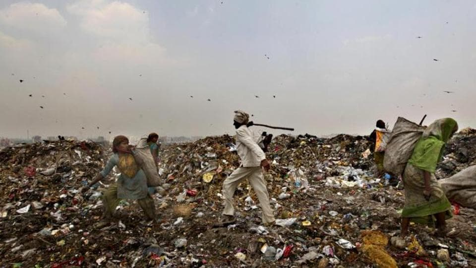 An civic body worker chases away ragpickers with a stick at the Ghazipur landfill site in east Delhi.