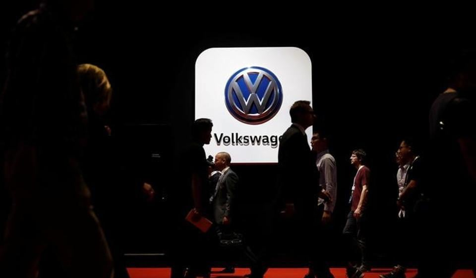 People pass in front of a Volkswagen logo at Shanghai Auto Show during its media day, in Shanghai.