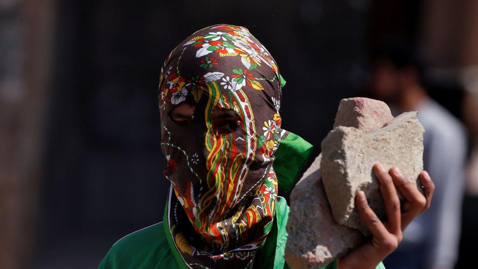 A masked protester holds stones during a protest in Srinagar