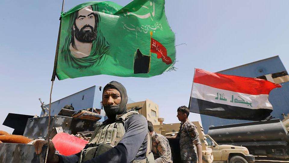 A Shia fighter stands next to a religious flag near Falluja, Iraq. The PMF is not officially involved in Syria, but tens of thousands of Iraqi Shia militiamen are fighting there on behalf of the government of President Bashar al-Assad.