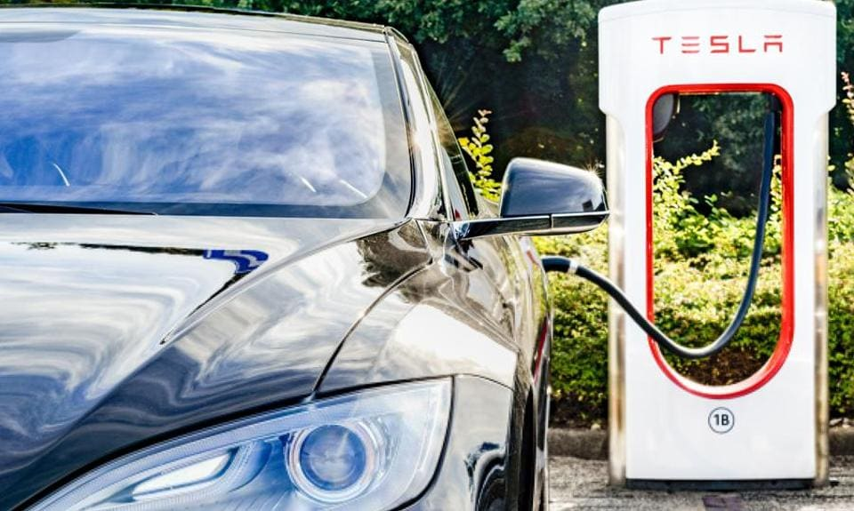 The Black Tesla Model S electric car at a Tesla supercharger charging station. Superchargers are free connectors that charge Model S in minutes. Tesla and Uber (and Ola in India) are current and future providers of public transport networks without which cities will be unable to do business.