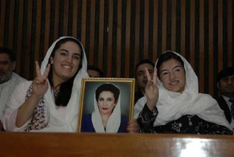 Bakhtawar Bhutto-Zardari (L) and sister Asifa with their mother's portrait.