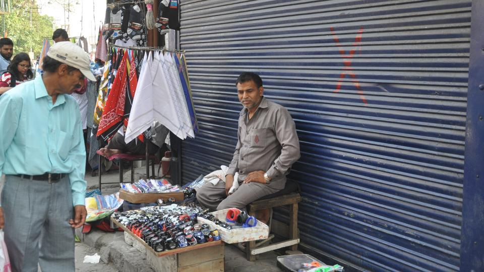 A street vendor sells goods outside a shop that has been marked for encroachment near Clock Tower in Dehradun.
