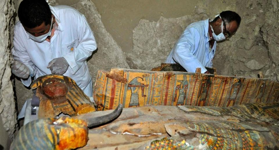 Members of an Egyptian archaeological team work on a wooden coffin discovered in a 3,500-year-old tomb in the Draa Abul Nagaa necropolis, near the southern Egyptian city of Luxor, on April 18.