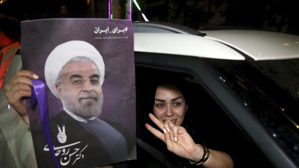 A supporter of Iran's President Hassan Rouhani, who is running for a second term in office, makes a V sign as she holds a poster of Rouhani in a car in Tehran, Iran, Friday, May 12, 2017.
