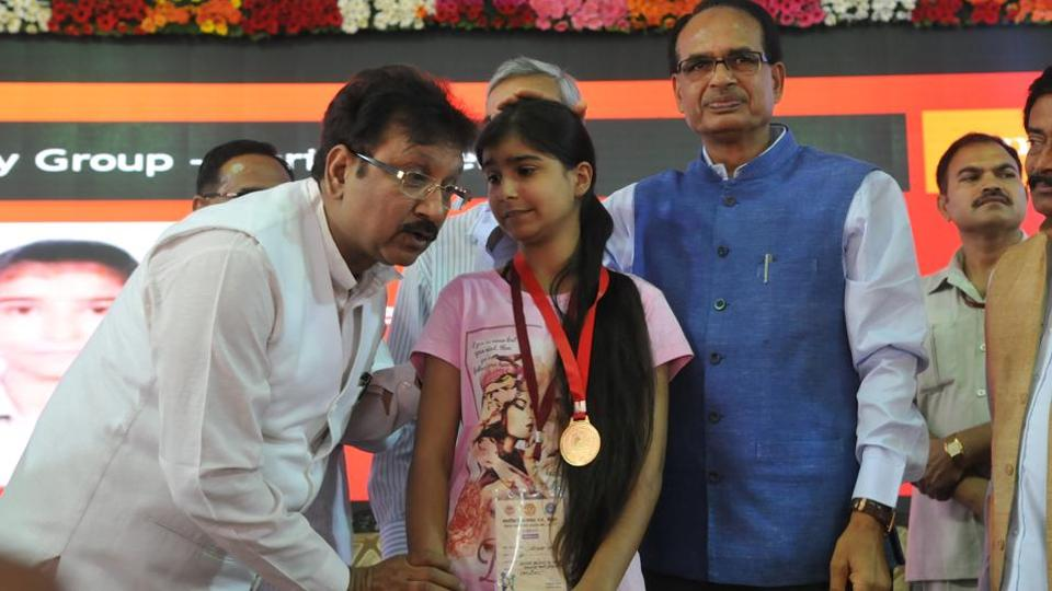 Madhya Pradesh School education minister Kunwar Vijay Shah with a topper, in the presence of chief minister Shivraj Singh Chouhan, during felicitation function of  meritorious students of the MP state board examinations in Bhopal on 12.