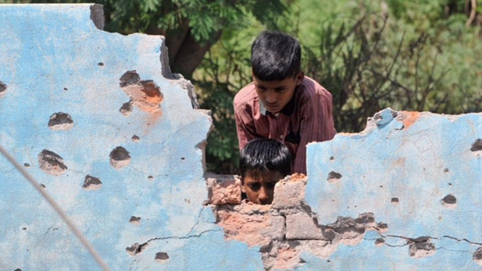Children inspect a house damaged by mortar shells at Jhanghar village in Nowshera.