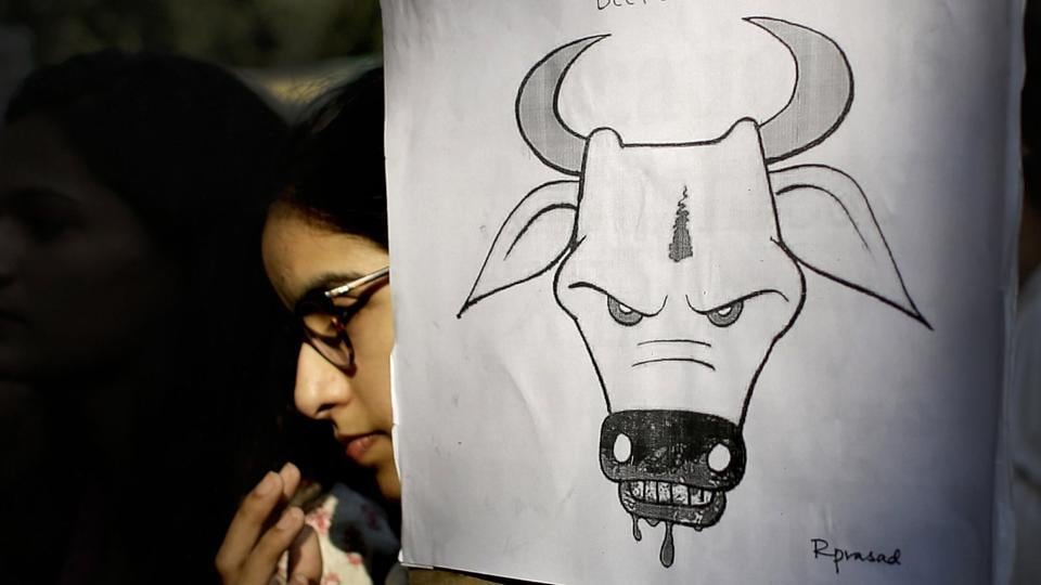 A student activist holds a placard during a protest denouncing cow vigilantism and killing of people in the name of cow protection in New Delhi.