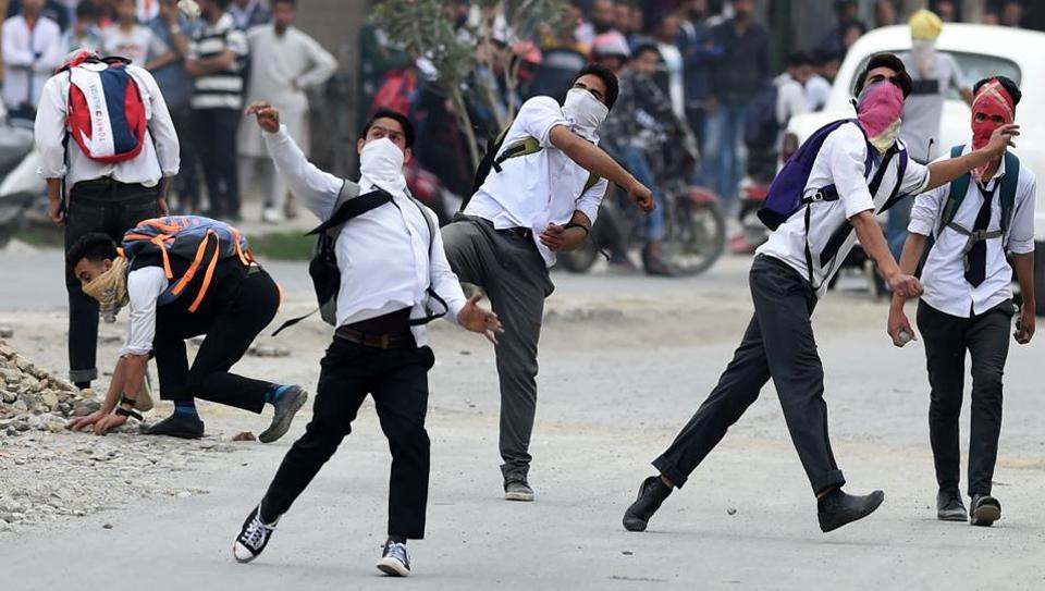Masked Kashmiri students throw stones during clashes with police in Srinagar on Thursday.