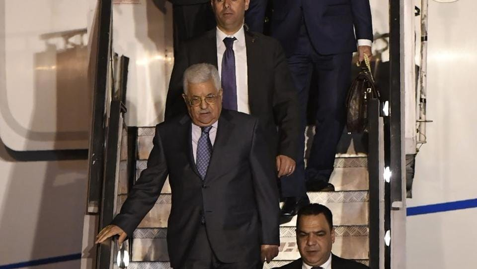 Palestine President Mahmoud Abbas (C) walks with officials as he disembarks from an aircraft after arriving at Palam Air Force Station in New Delhi on May 14.