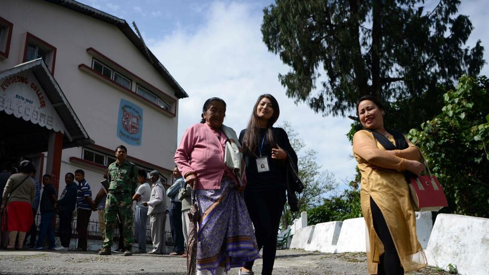 An elderly voter is assisted by volunteers after casting her vote at a polling station in Kurseong on Sunday  for local municipal elections.