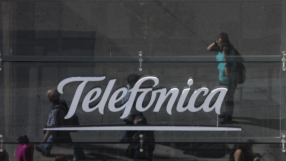 People are reflected in a glass sign of a Telefonica building in Madrid, Spain, Saturday, May 13, 2017. The Spanish government said several companies including Telefonica had been targeted in ransomware cyberattack that affected the Windows operating system of employees' computers.