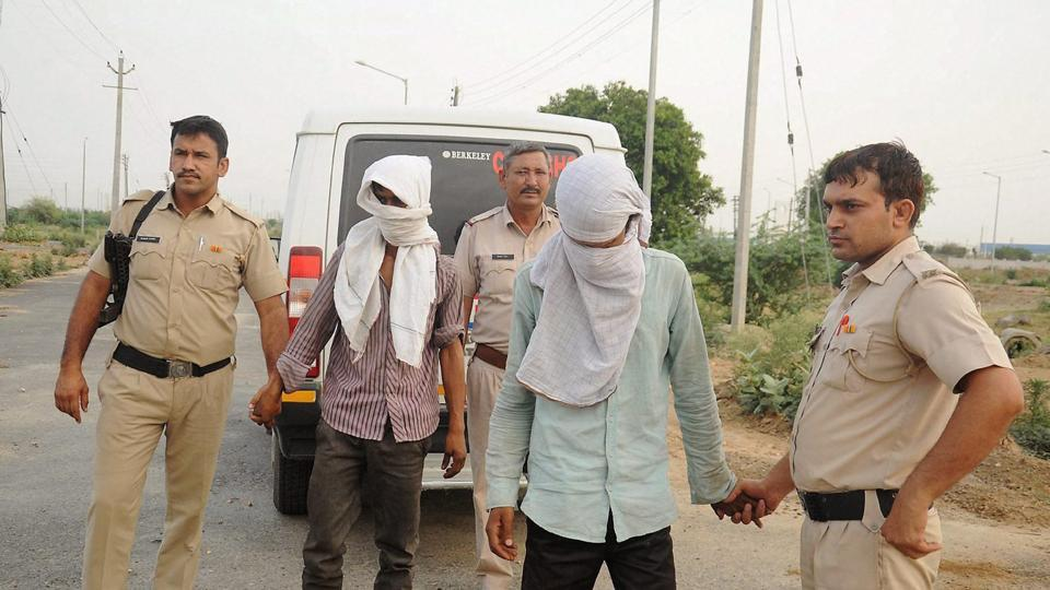 Police take the accused to the scene of the crime where they allegedly dumped a woman's body after raping her in Rohtak.