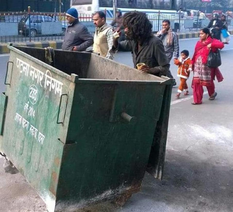 A man searches for leftover food from a garbage bin in Patna.