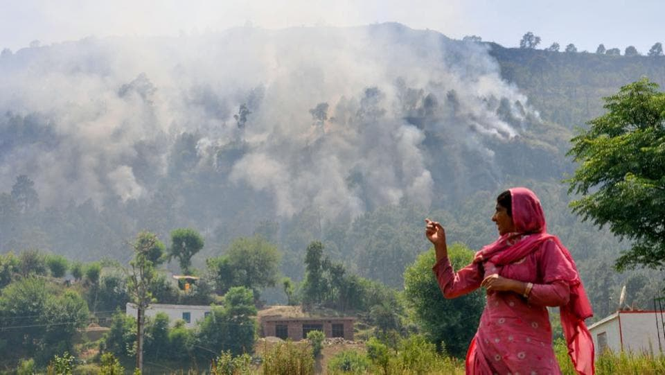 A lady points at smoke caused by firing of mortar shells from the Pakistan side of the border.