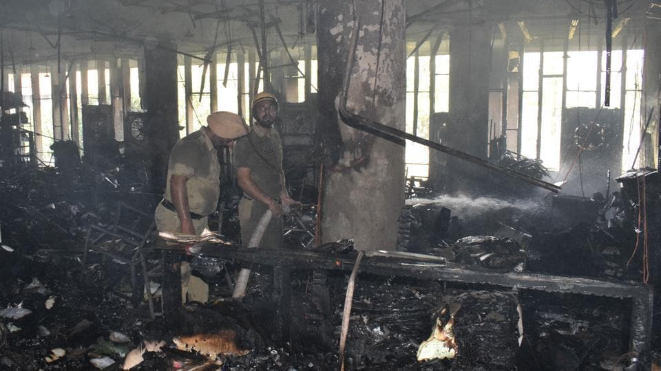 Fire fighters dousing the fire at the administrative block of Panjab University in Chandigarh on Sunday.