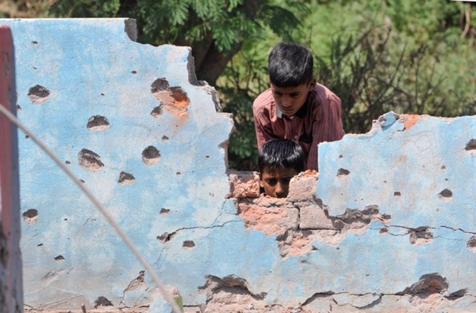 Children at a house damaged by mortar shells fired from the Pakistan side of the border, at Jhanghar village, in Nowshera.