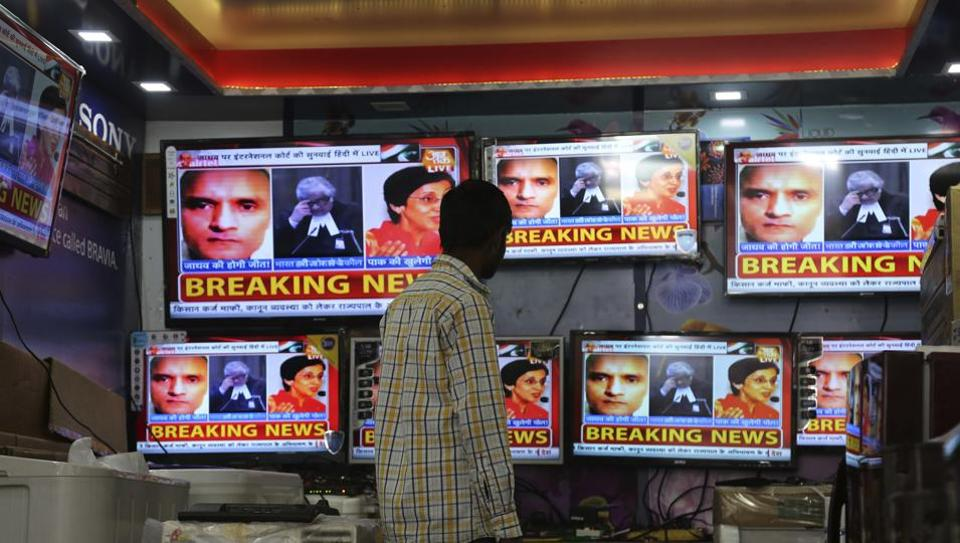An Indian boy watches as television channels show news about International Court of Justice hearing the case of Indian naval officer Kulbhushan Jadhav at a shop in Jammu on May 15.