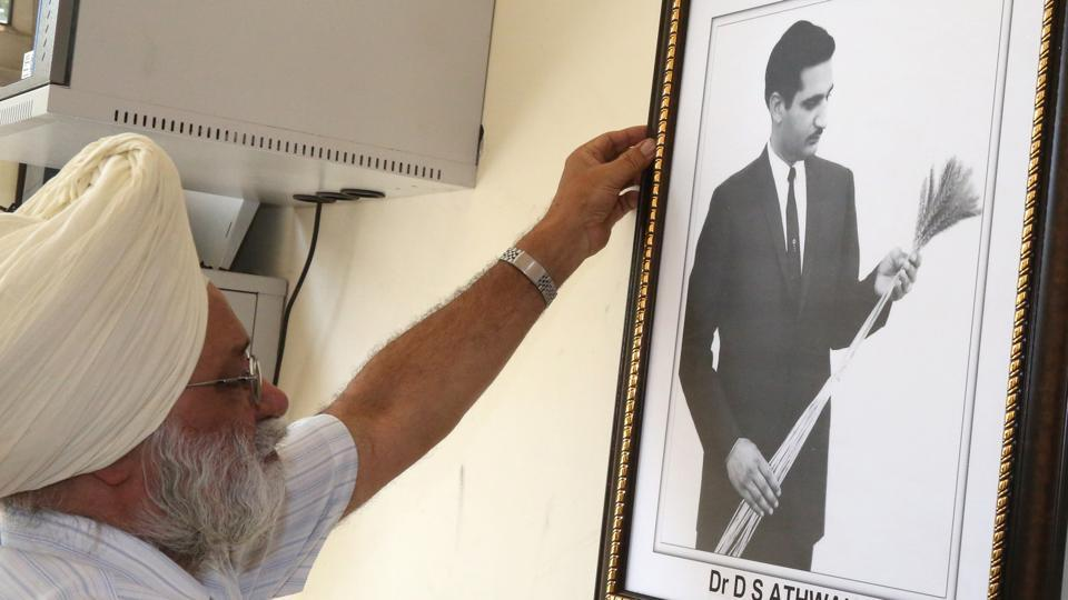 A staff member with a portrait of Dilbagh Singh Athwal at PAU in Ludhiana on Monday, May 15.