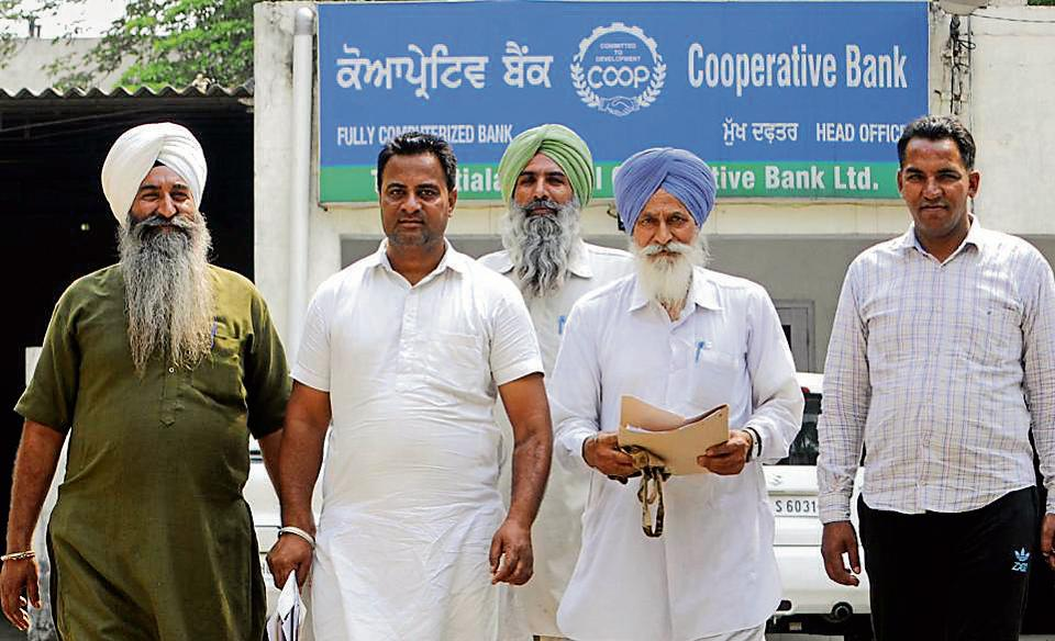 Farmers coming out of the Central Cooperative Bank in Patiala on Monday.