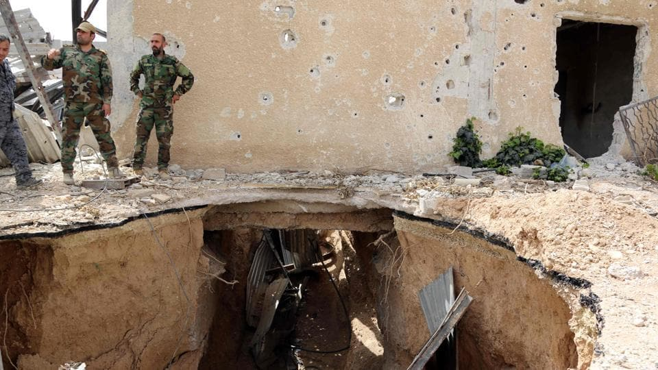 Syrian government forces inspect a destroyed tunnel in Damascus' north eastern al-Qaboun suburb on Sunday.