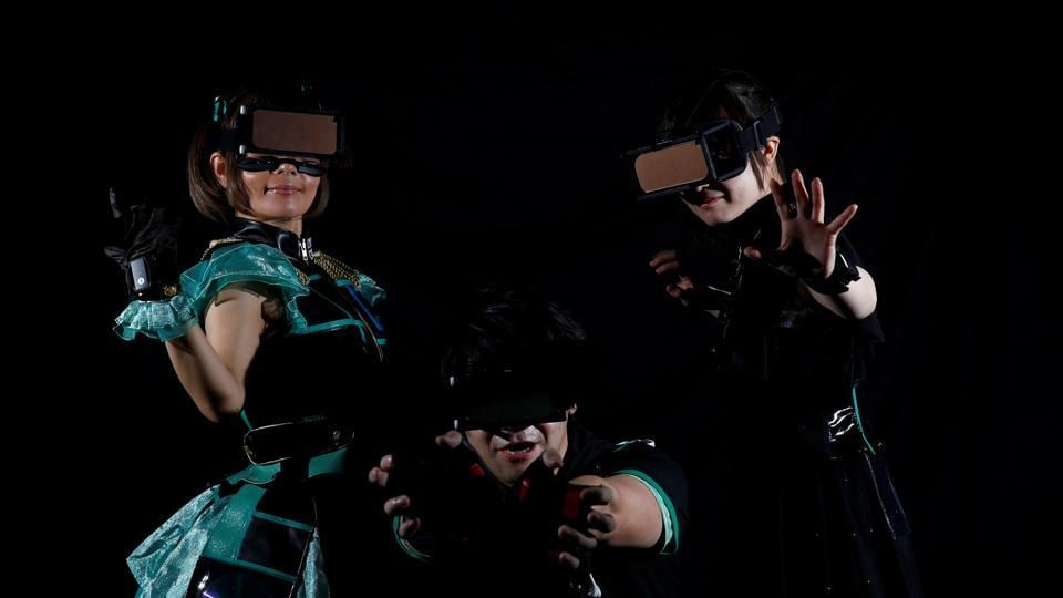 Piyohina, Junpei Sasaki, Rimiko Sakihama (L-R), members of HADO team 'Slamdiva', pose for a photograph wearing head-mount displays and armband sensors in Tokyo, Japan. (REUTERS)