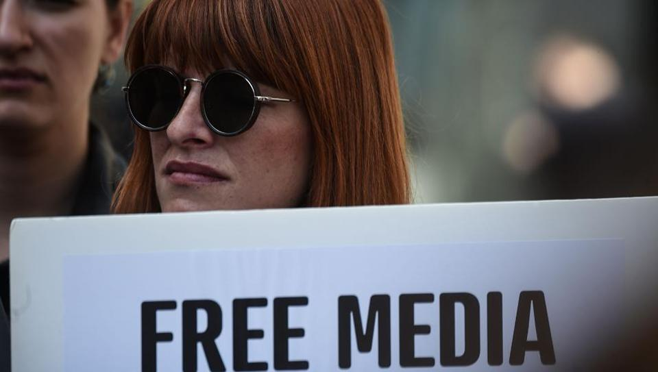 A journalist holds a placard reading