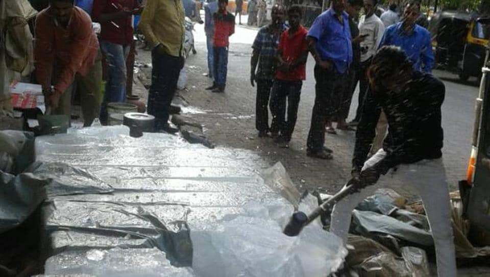 A civic worker destroys blocks of contaminated ice in Mumbai.