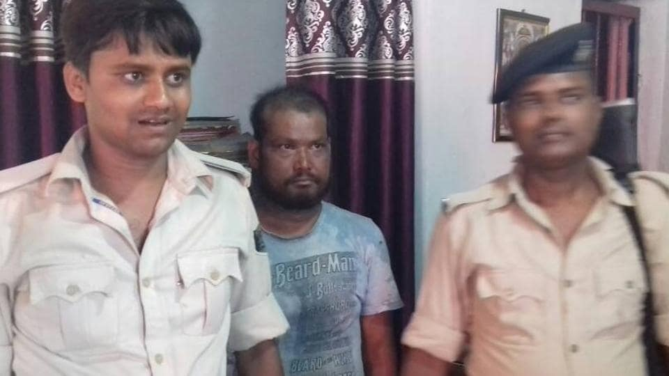 Mohammad Mustaque (centre), accused of killing his eight -year-old daughter, in police custody.