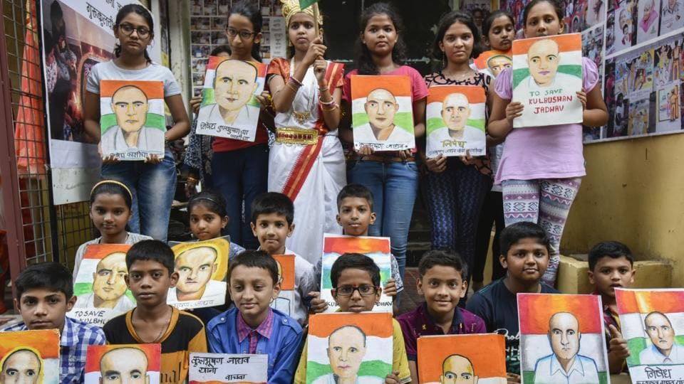 Students pose with paintings of Kulbhushan Jadhav during a protest in Mumbai.