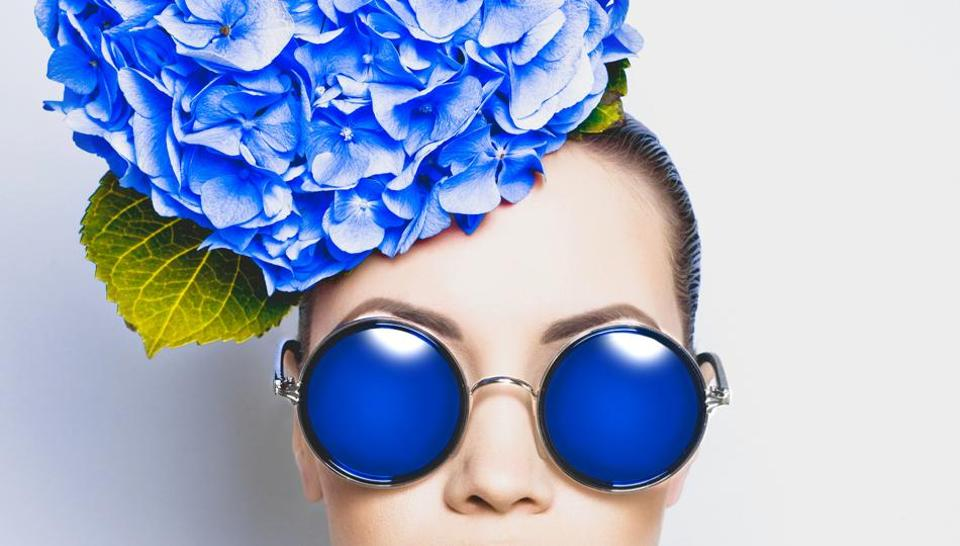 Fashion portrait of beautiful young lady with blue hydrangea