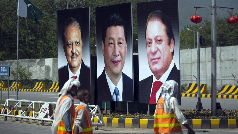 Workers walk past a billboard showing pictures of Chinese President Xi Jinping (centre) with Pakistan's President Mamnoon Hussain and Prime Minister Nawaz Sharif during a two-day visit by Xi to launch the economic corridor linking Pakistan's port city of Gwadar with western China.