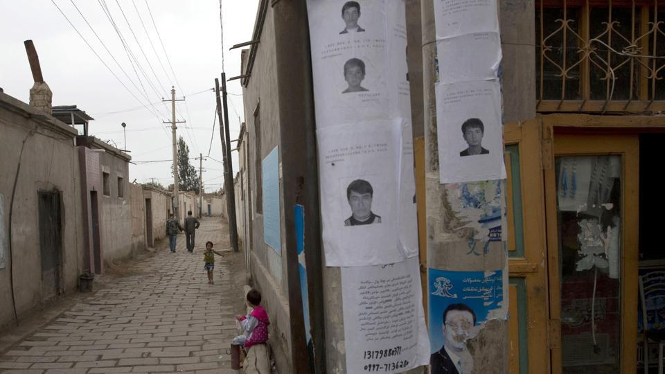 In this July 2014 file photo, wanted posters of men involved in terror attacks are posted on a street of Aksu in western China's Xinjiang province. Human Rights Watch said on May 16, 2017 that China appears to be laying the groundwork for the mass collection of DNA samples from residents in the restive region with a large Muslim population.