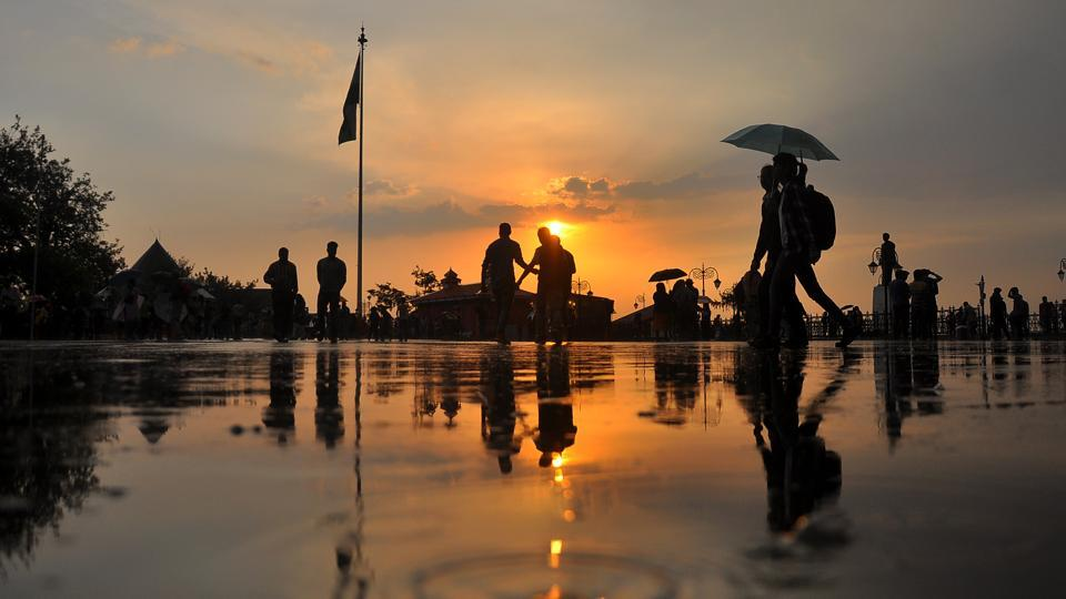 People enjoy an evening walk overlooking a beautiful sunset in Shimla after light showers lowered the temperature. Thunderstorms accompanied with squall and hail have been predicted by IMD in the next couple of days. (Deepak Sansta / HT Photo)