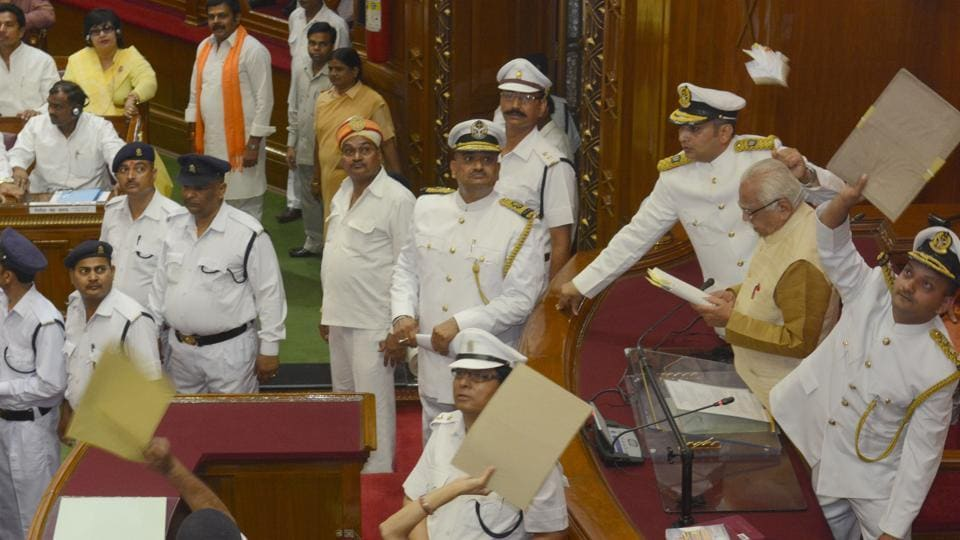 Marshals deflecting paper balls thrown by opposition members at governor Ram Naik on the first day of the state assembly session in Lucknow on Monday.