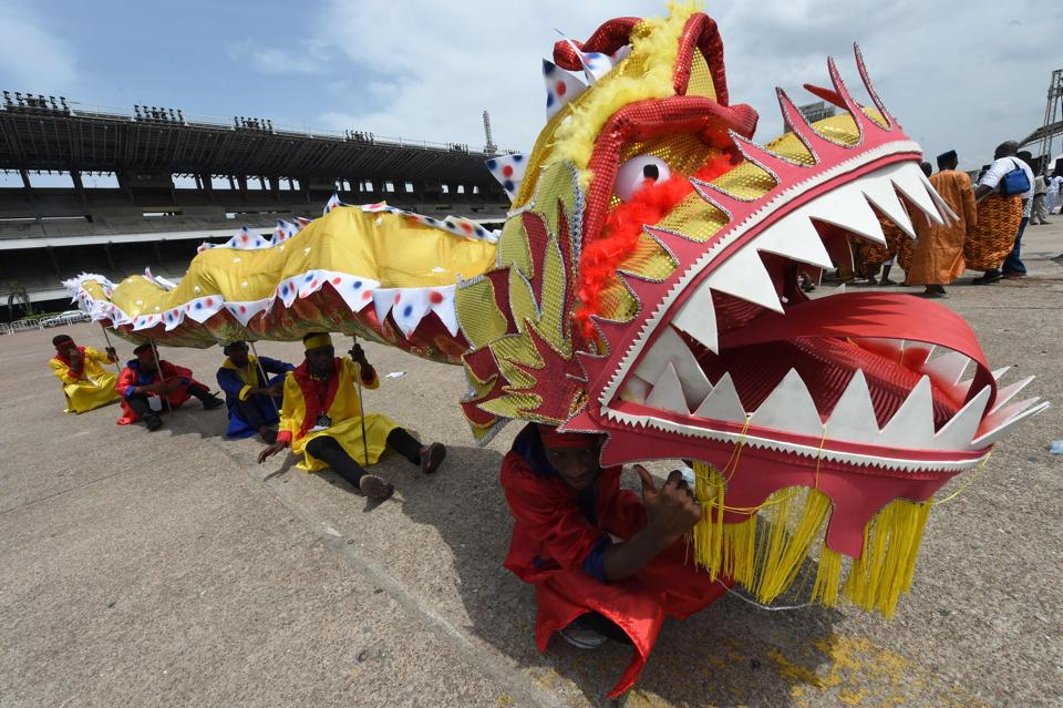 People perform with A Chinese dragon during a carnival . (PIUS UTOMI EKPEI / AFP)