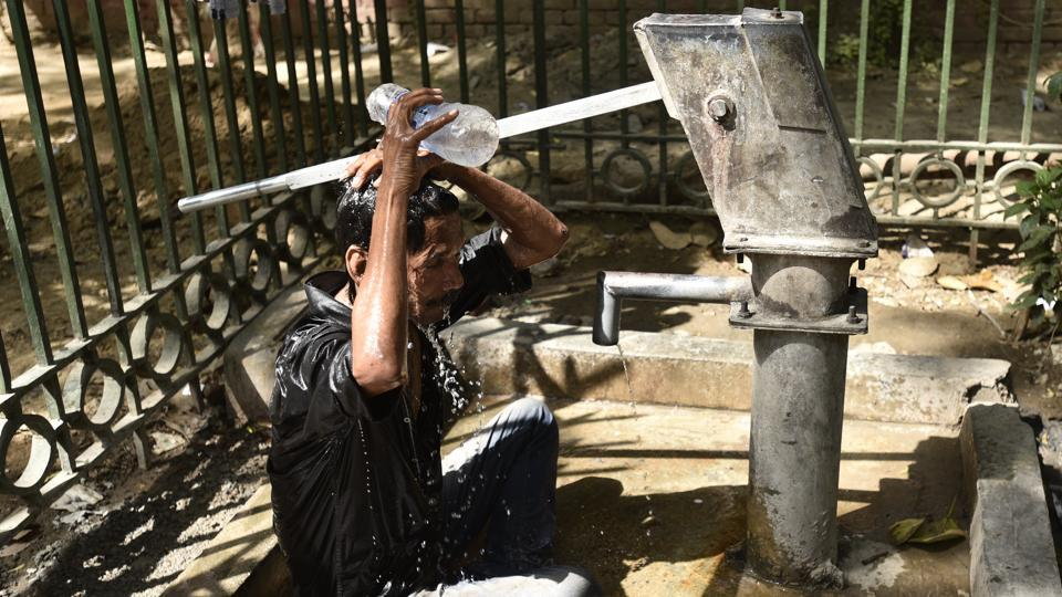 A man cools off on a roadside hand pump on a hot summer day in New Delhi on Monday.