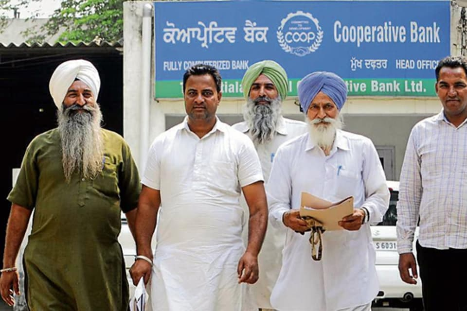 Farmers coming out of the Central Cooperative Bank in Patiala.