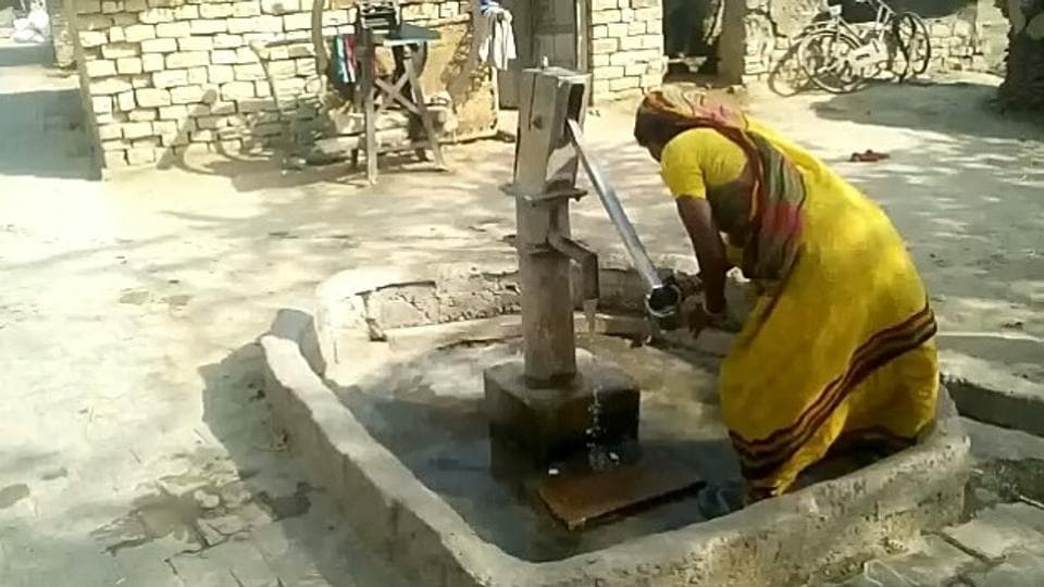 A woman drawing water from the only handpump in the village.