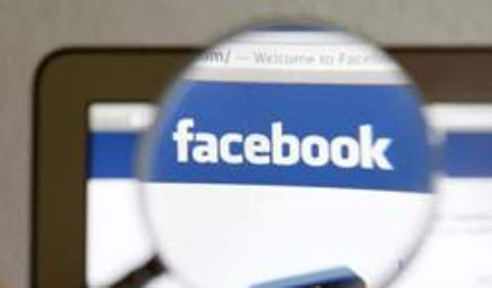 A Facebook logo on a computer screen is seen through a magnifying glass held by a woman in Bern.