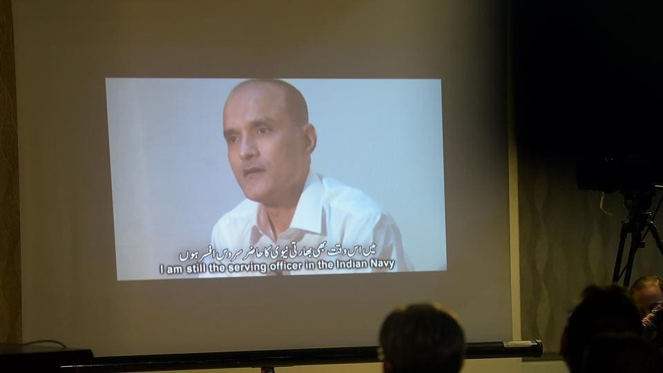 Journalists watch a video showing Indian national Kulbhushan Yadav during a press conference in Islamabad.