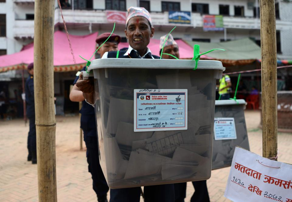 A Nepalese election worker carries a sealed ballot box after polling stations closed in Kathmandu on Sunday.