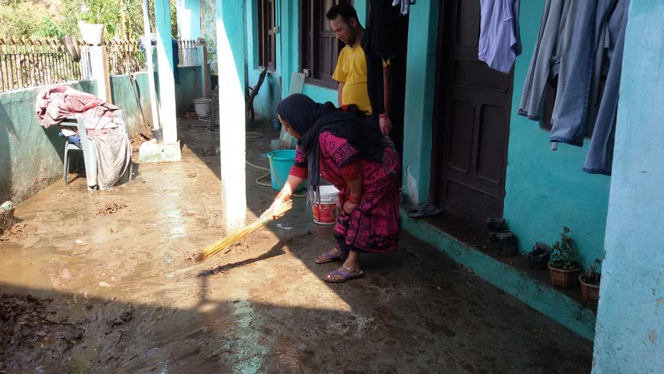A woman cleans the silt that entered her house following heavy rainfall in Narayan Nagar village on Wednesday.