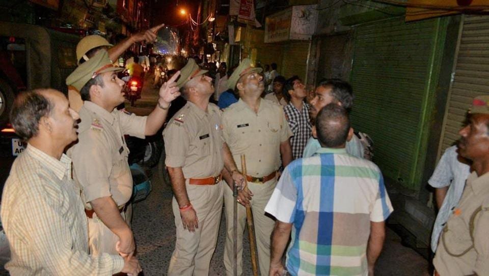 Police inspect a jewellery shop after it was attacked by robbers in Mathura.