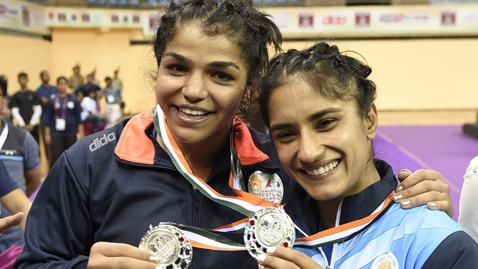 Sakshi Malik (L) and Vinesh Phogat pose with their silver medals at the Asian Championship in New Delhi.