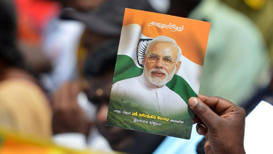 Prime Minister Narendra Modi wave flags and posters at a public rally.